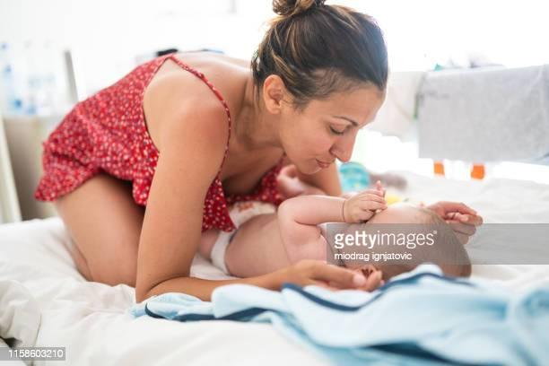 mother changing diaper to sleepy baby boy - mum changing nappy stock pictures, royalty-free photos & images