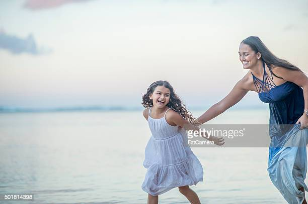 mother chasing her daughter down the beach - kids playing tag stock photos and pictures