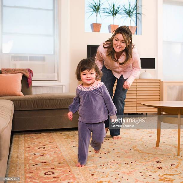 Mother chasing little girl at home