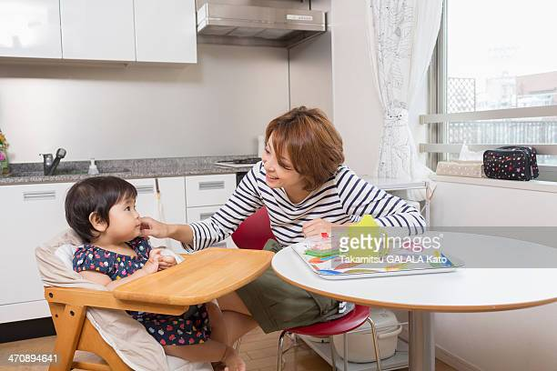 Mother chatting to baby at dining table