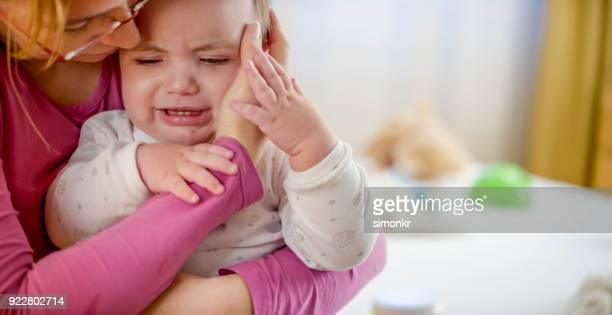 mother checking baby's temperature with her hand - moms crying in bed stock photos and pictures
