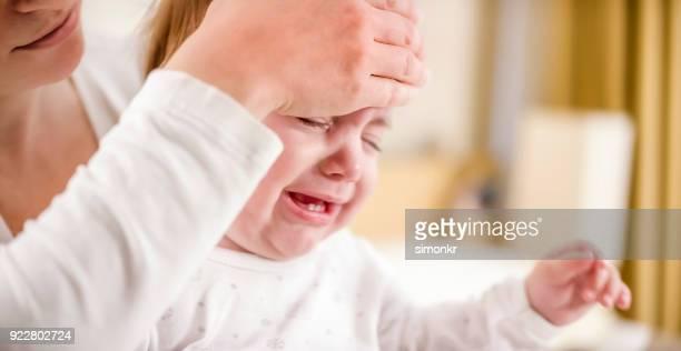 moeder controle baby's temperatuur met haar hand - ziekte stockfoto's en -beelden