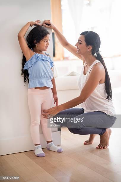 mother checking daughters height - lang lengte stockfoto's en -beelden