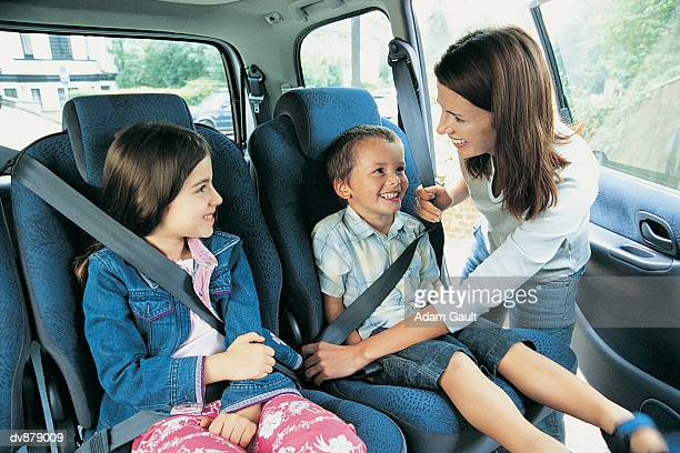 Mother Checking Her Children's Seatbelts in a Car