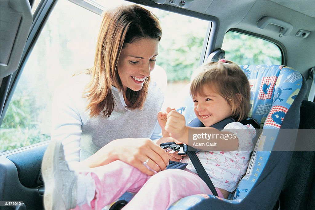 Mother Checking Her Toddler's Child Seat in a Car : Stockfoto
