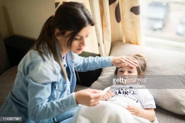 mother checking on sick daughter laying in bed - family with one child stock pictures, royalty-free photos & images