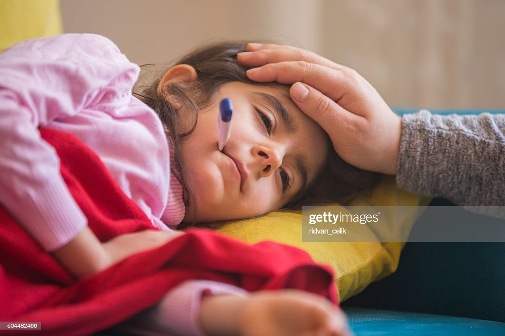 Mother checking on sick daughter laying in bed : Stock Photo