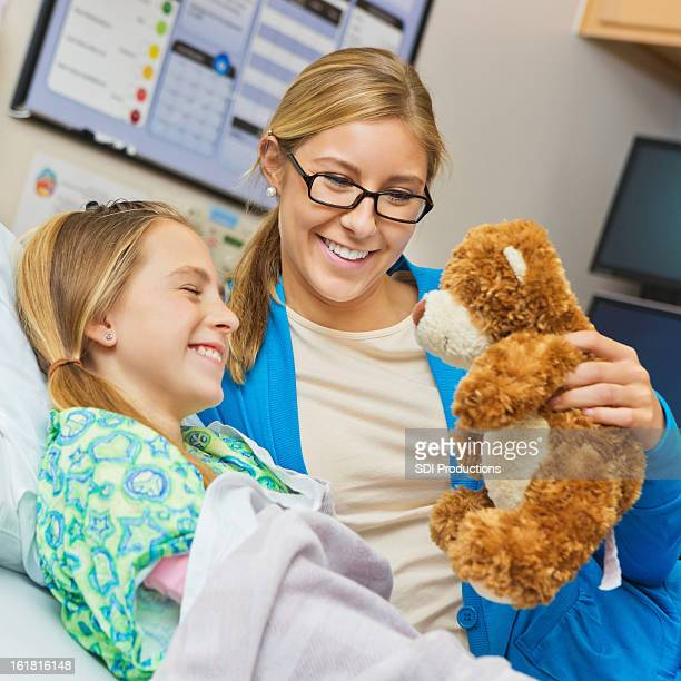 Mother cheering up sick daughter in hospital