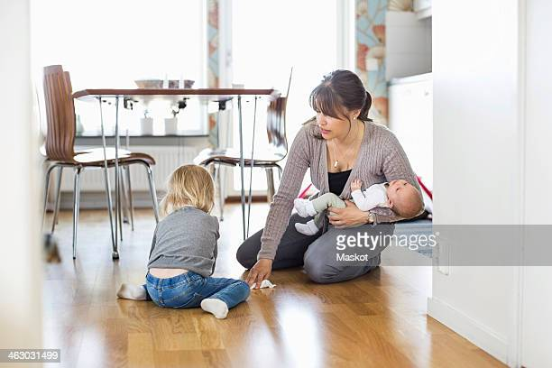 Mother cleaning floor with daughter while holding baby at home