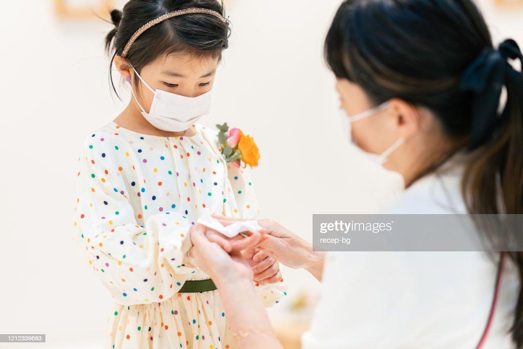母親はウイルスから彼女の子供を保護するために濡れたアルコール組織で彼女のドーガーの手を掃除 : ストックフォト