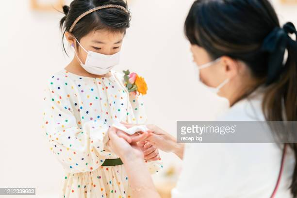 mother cleaning her daugher`s hands with wet alcohol tissue to protect her child from viruses - antiseptic stock pictures, royalty-free photos & images