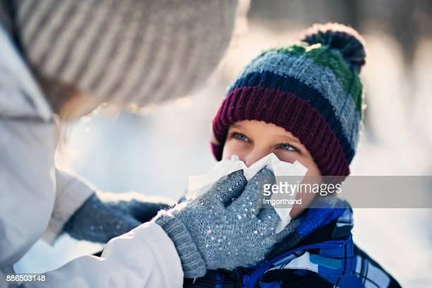 mère nettoyage nez de malade le jour de l'hiver - handkerchief photos et images de collection