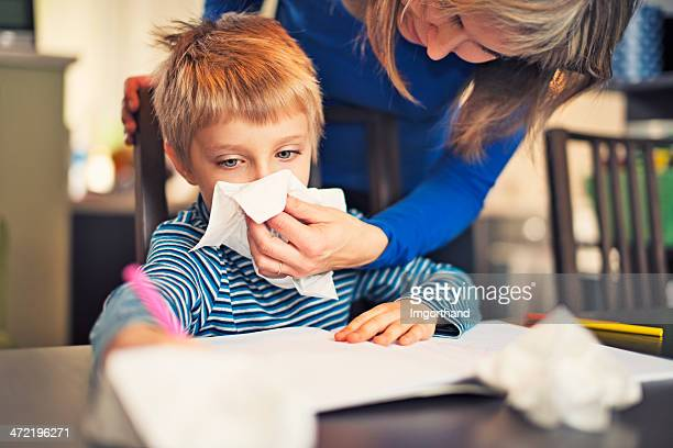 Mother cleaning nose of sick son