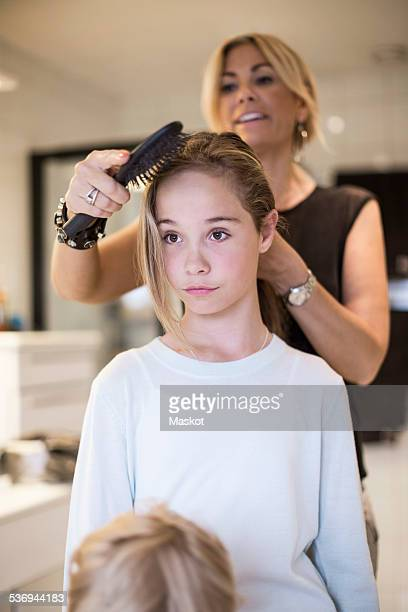 Mother combing daughters hair at home