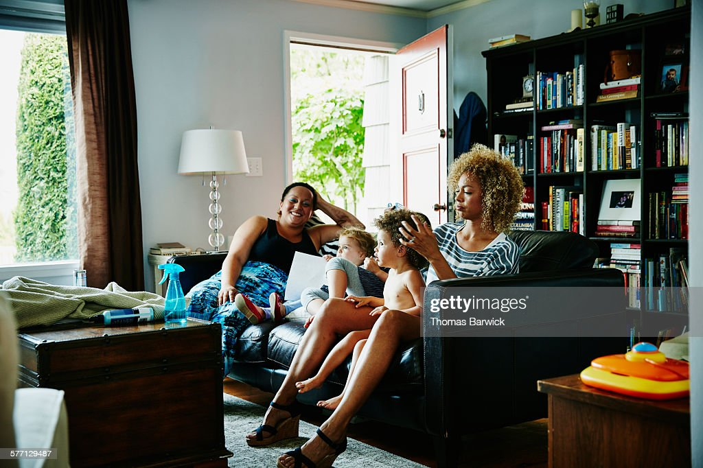 Mother combing daughters hair in living room : Stock Photo