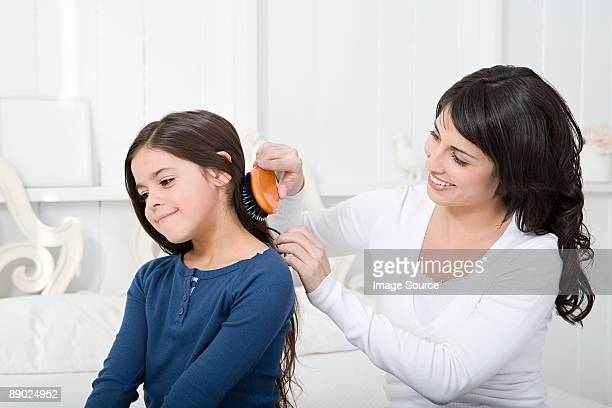 Mother combing daughters hair