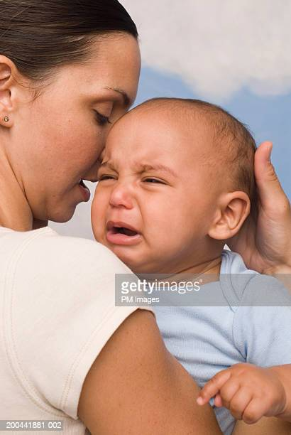 Mother comforting crying baby boy (3-6 months)
