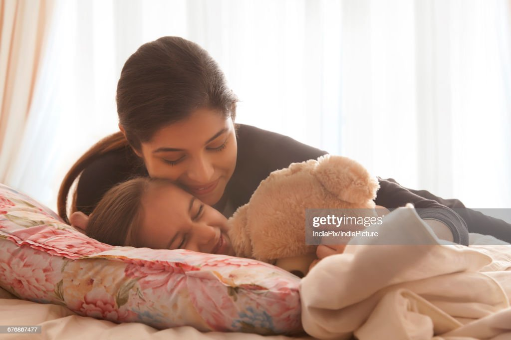 Mother comforting daughter in bed : Stock Photo