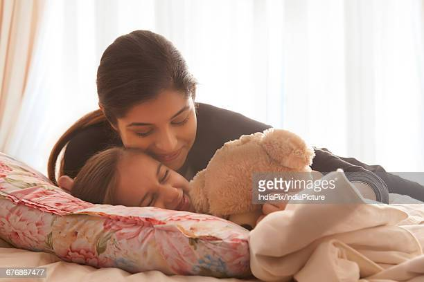 mother comforting daughter in bed - indian girl kissing stock photos and pictures
