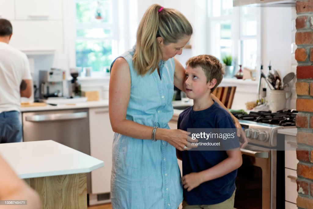 Mother comforting son in home kitchen. : Stock Photo