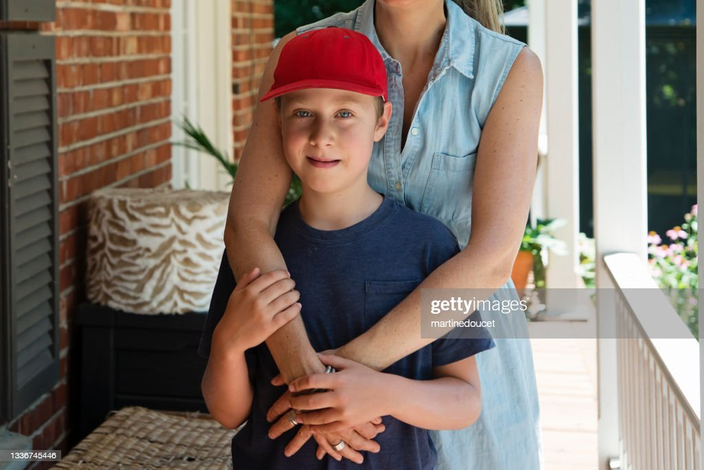 Mother comforting son on home porch. : Stock Photo