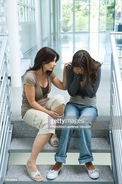 Mother comforting teenage daughter, sitting on steps