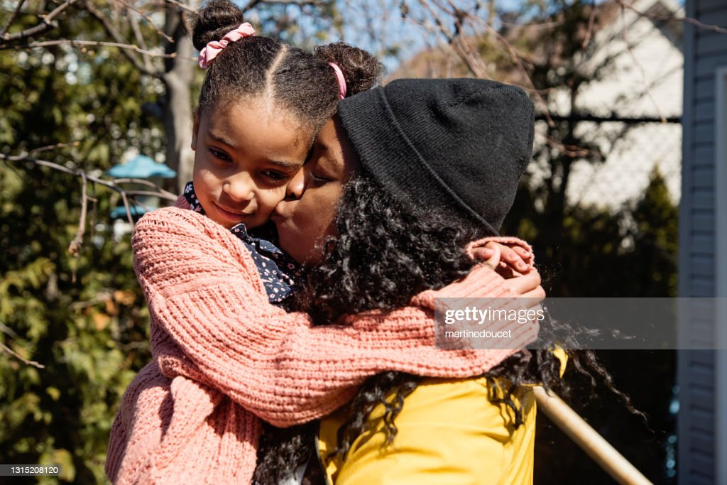 Mother comforting young daughter outdoors in springtime. : Stock Photo