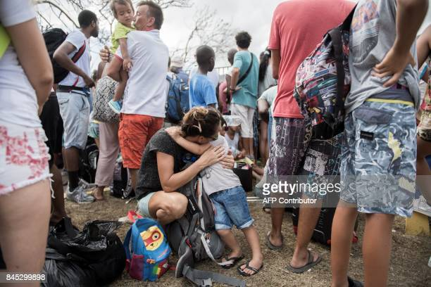 TOPSHOT A mother comforts her child as they wait in front of GrandCase Esperance airport entrance to leave SaintMartin on September 10 2017 on the...