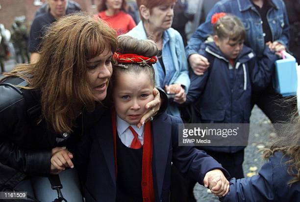 A mother comforts her daughter in the aftermath of a blast bomb attack while on the way to school September 5 2001 in North Belfast The bomb was...