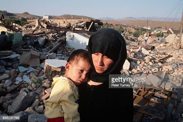A mother comforts her son after a severe earthquake laid their town to waste Casualty estimates have reached as high as 20000