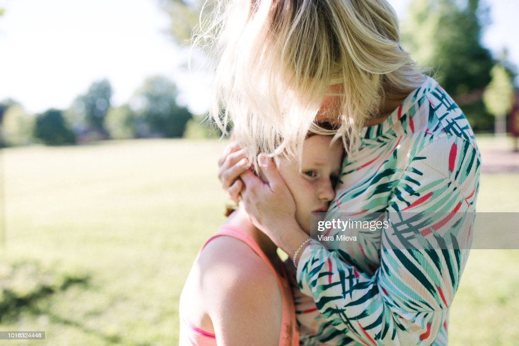 Mother consoling daughter in park : Stock Photo