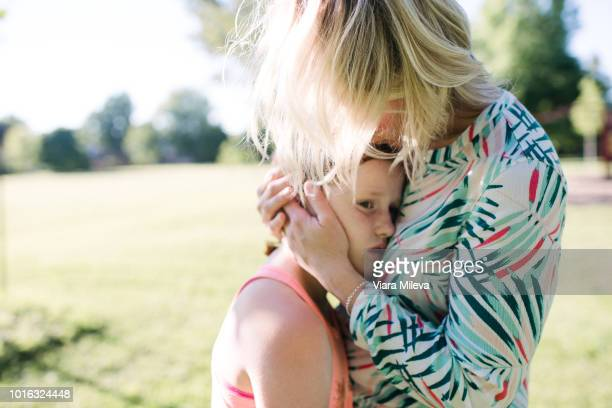 mother consoling daughter in park - sad mom stock pictures, royalty-free photos & images