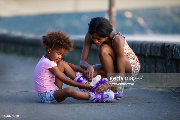 mother consoling her daughter who fell while roller skating - inline skating stock pictures, royalty-free photos & images