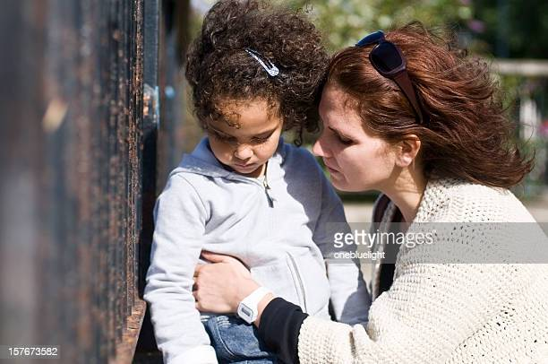 Mother consoling unhappy 4 year old daughter