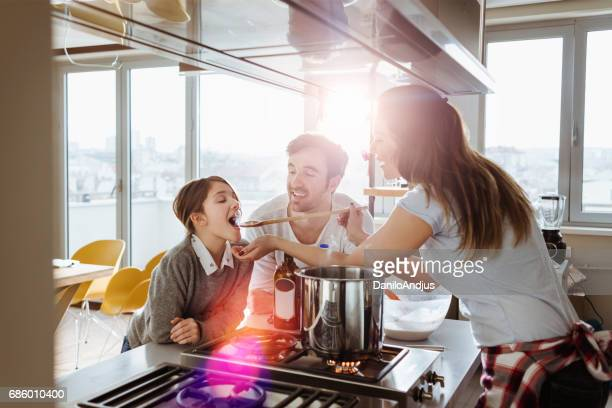 Mutter kochen und geben ihrer Tochter zu versuchen
