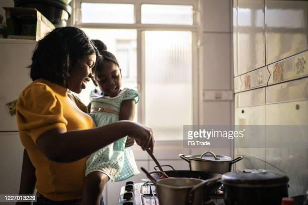 mãe cozinhando em casa enquanto segura sua filha - preparing food - fotografias e filmes do acervo