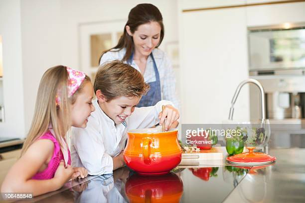 Mother cooking food with children (8-11) in kitchen