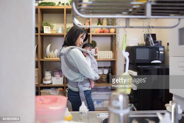 Mother cooking in kitchen with baby
