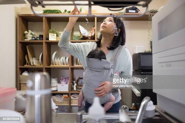 赤ちゃんとの台所で調理の母 - シングルマザー ストックフォトと画像