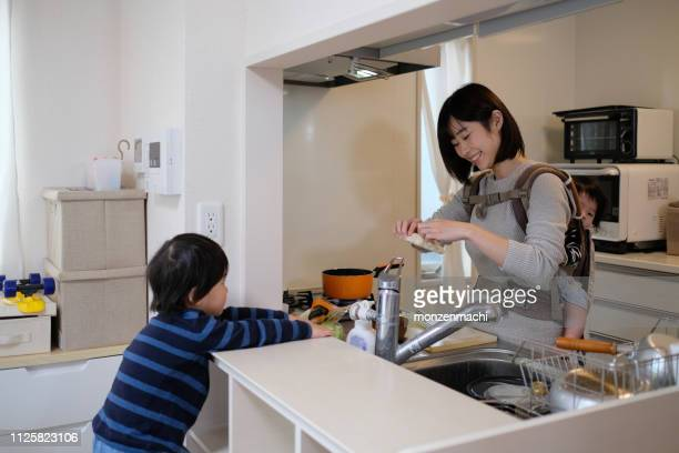 mother cooking with baby on her back in kitchen - stay at home mother stock pictures, royalty-free photos & images