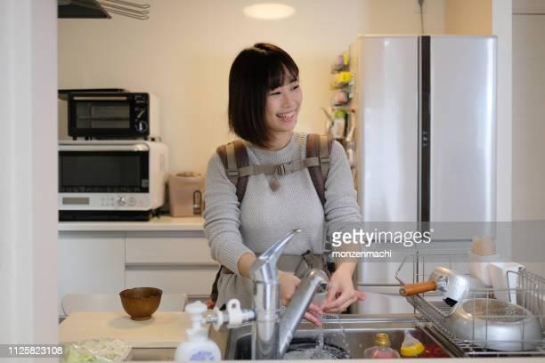 母親が台所であおむけに赤ちゃんと一緒に料理 - 専業主婦 ストックフォトと画像