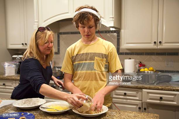 Mother cooking with teenage son