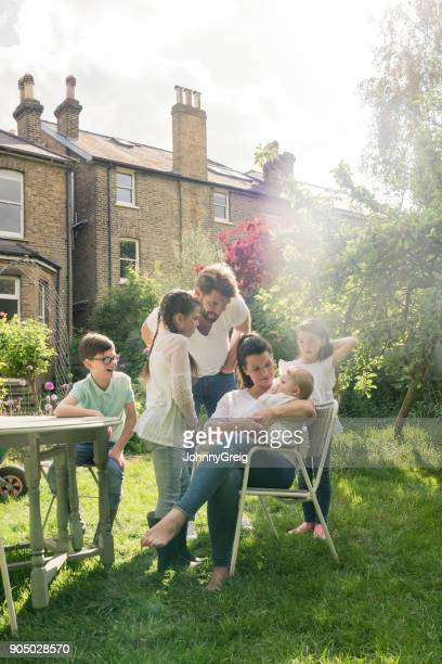 Mother cradling baby boy on garden chair, father and older siblings watching