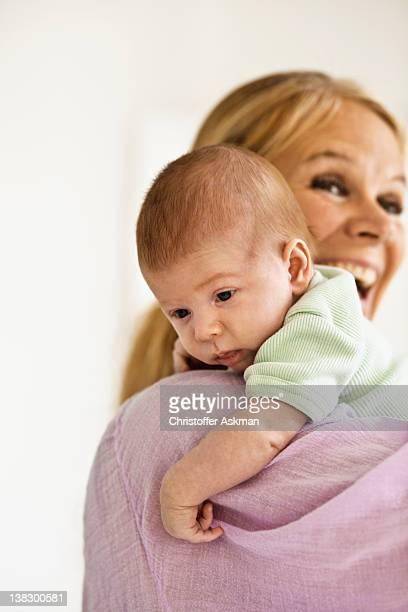 Mother cradling infant on shoulder