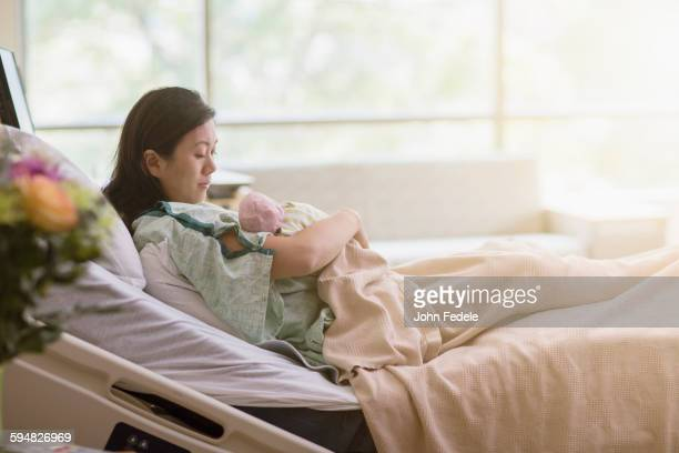Mother cradling newborn baby in hospital room