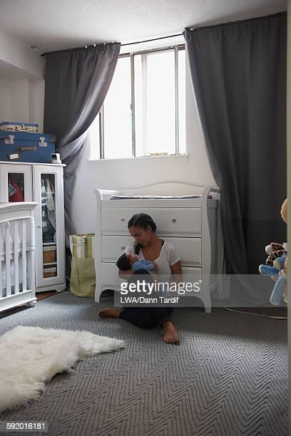 Mother cradling newborn baby in nursery