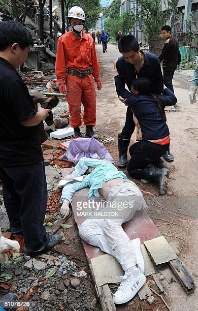 A mother cries as rescue workers remove the body of a child when a high school collapsed after a 78 magnitude earthquake hit the town of Hanwang in...