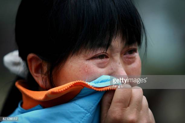 A mother cries for her son near the ruins of the Beichuan Middle School during the one year anniversary of the Wenchuan Earthquake that caused the...