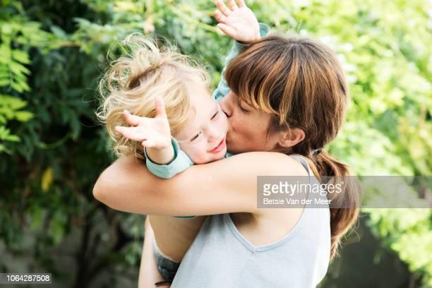 mother cuddles and kisses toddler in garden. - kleinstkind stock-fotos und bilder