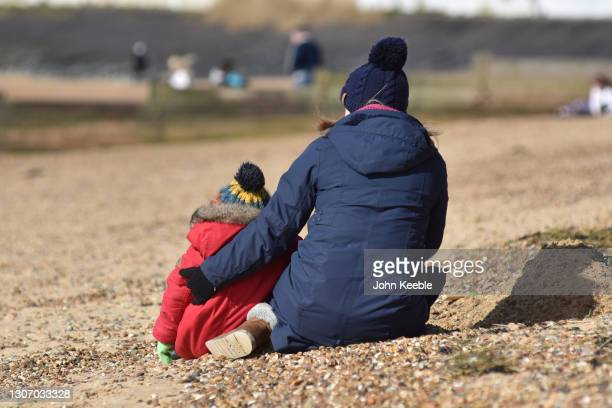 Mother cuddles her son while they sit on Chalkwell beach on Mothering Sunday on March 14, 2021 in Southend-on-Sea, England.